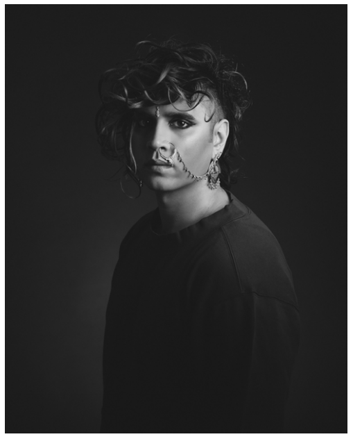 A black and white picture of trans bisexual activist Vivek Shraya with curly hair and an undercut. Vivek has beautiful dark eyes and is wearing a nath, an elaborate nose ring that is attached to her earring.